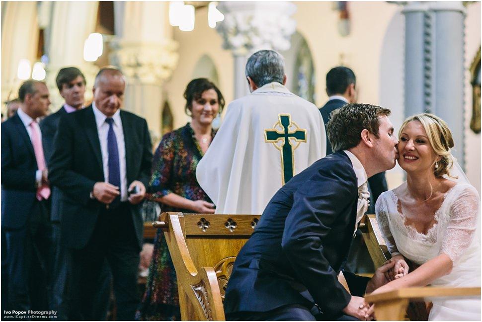 Groom kissing bride in church in Emly