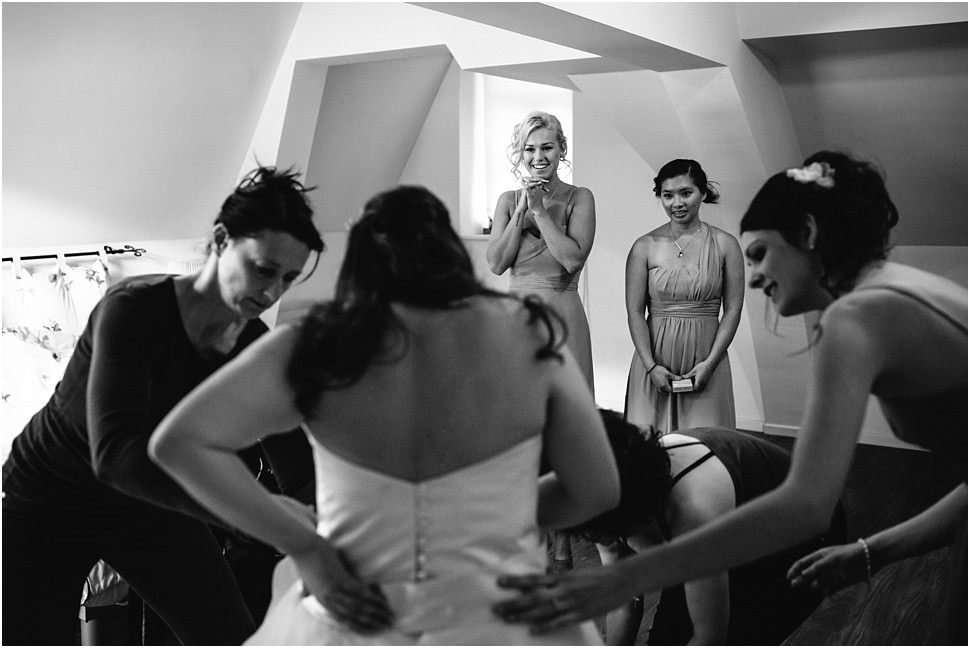 Bride putting in the wedding dress while bridesmaids watching in Antwerpen