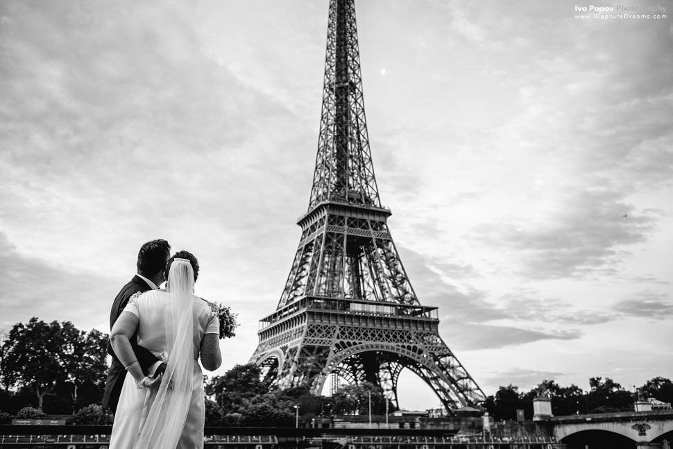 Bride and groom looking at the Eiffel Tower in Paris
