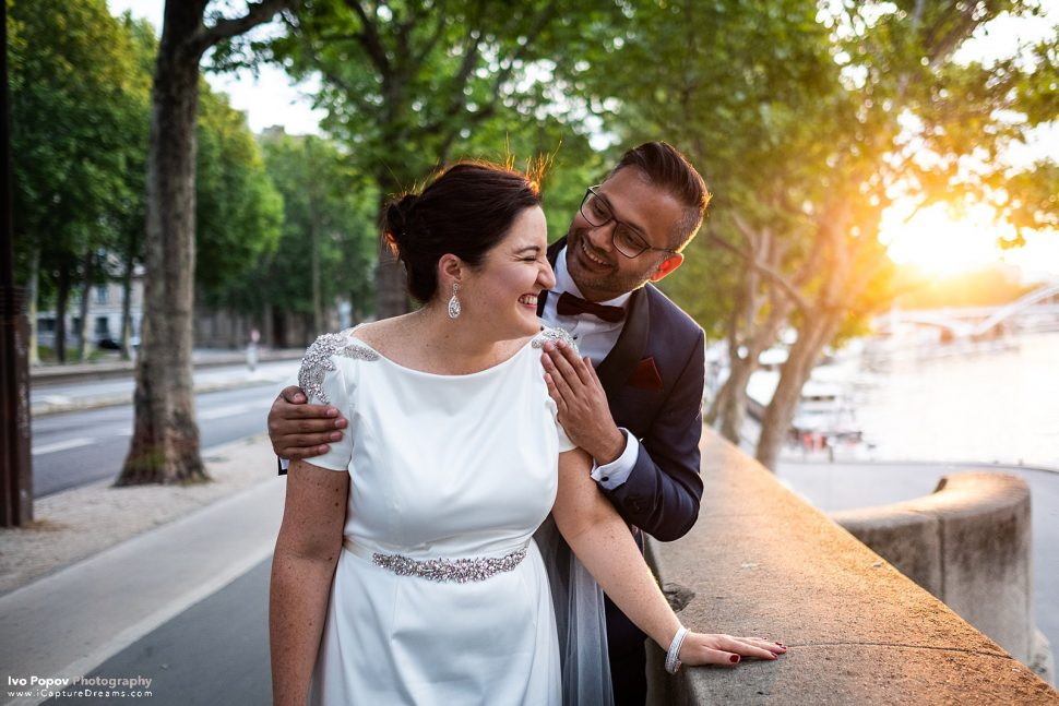 Bride and groom walking alongthe Seine river in Paris at sunrise